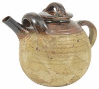 A large pottery teapot with streaked brown glaze to lid and spout, stamped on the