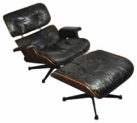 A Charles and Ray Eames rosewood and black leather lounge chair and ottoman (a.f) approximately