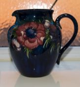W Moorcroft Signed Globular Jug 'Clematis' design on blue ground circ 1940's 6.5 inches high.