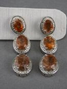 Tanzanian Sunstone Triple Drop Earrings, each earring having three graduated oval cut sunstones, a