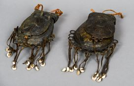 Two African cast bronze pouches Both with decorated flaps and pendant cowrie shells.