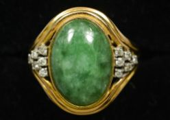 A 14 ct gold jade and diamond set ring The central cabochon jade stone flanked by small diamonds.