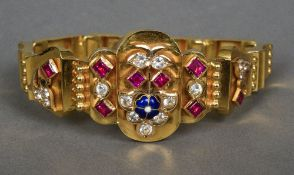 An unmarked high carat gold, ruby, clear sapphire and enamel set bracelet 17.5 cm long.