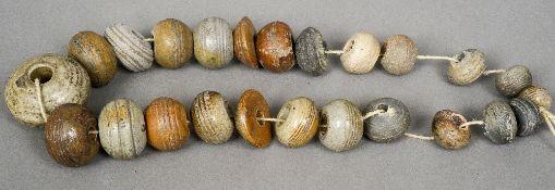 A string of twenty-five 18th century salt glaze spinning weights Each typically modelled.