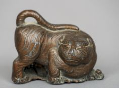 A Chinese bronzed lead tiger  Modelled crouching before bamboo sprays.  7 cm long.
