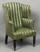 A Victorian mahogany wing back armchair With green striped upholstery,