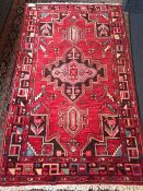 A Caucasian wool rug The wine red field enclosing a central medallion with pendant palmettes within