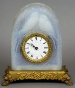 An early 20th century Lalique style opalescent pressed glass mantel clock The domed case with two