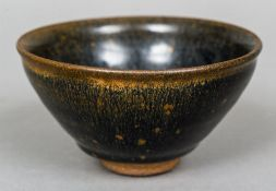 An early Chinese pottery bowl With black and red glaze decoration.  12 cm diameter.