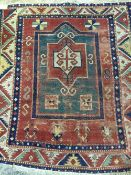 A Caucasian wool prayer rug The central mirhab field within geometric guard stripes and border.