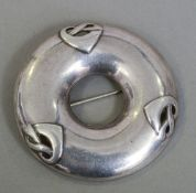 A Liberty & Co. silver brooch Of circular form, in the manner of Archibald Knox.  5.25 cm diameter.
