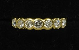 An 18 ct gold seven stone diamond ring Of band form, with pierced shoulders.