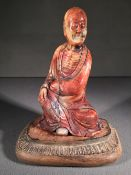 A Chinese carved hardstone figure of a sage Worked kneeling on a carved wooden  base.  14.5 cm high.