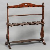 A 19th century mahogany whip and boot rack Of typical shaped trestle form,