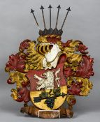 A carved and painted wood heraldic crest The shield worked with a lion and fruiting vine mounted