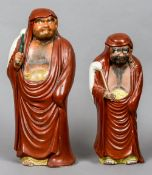 Two Japanese pottery figures Each formed as a hairy man wearing a red robe.  The largest 41 cm high.