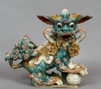 A Chinese pottery temple dog Typically modelled and decorated.  45 cm high.