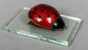 An early 20th century enamel decorated letter clip Formed as a ladybird mounted on a rectangular