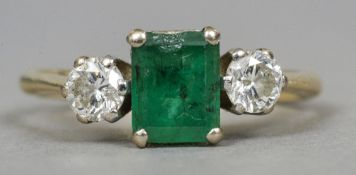 An 18 ct gold diamond and emerald ring The central emerald flanked by two claw set diamonds.