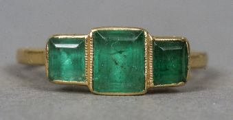 An 18 ct gold emerald set ring The square cut emeralds in pierced setting.