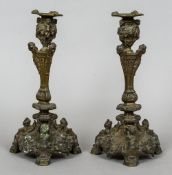 A pair of 19th century cast bronze candlesticks Each with cherub mask and caryatid decoration.