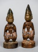 A pair of small Yoruba tribal figures Each modelled standing on a circular plinth base.