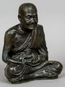 A Chinese bronze figure Modelled as a sage, seated cross legged.  28.5 cm high.