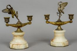 A pair of gilt bronze twin branch candelabra Each surmounted with the figure of a heron wrestling a
