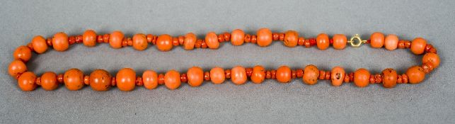 A string of coral beads Mounted with a gold clasp.  38 cm long.
