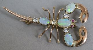 An unmarked gold brooch formed as a scorpion Set with opals and other various stones.  5.5 cm long.