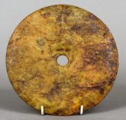 A Chinese carved hardstone bi-disc One side with elements of a carved motif.  19 cm diameter.