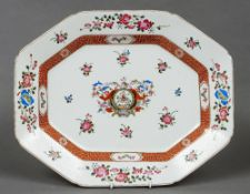 An armorial porcelain meat platter In the famille rose palette, of typical canted rectangular form.