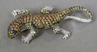 An 18 ct white gold brooch formed as a lizard  Set with diamonds and other semi-precious stones.