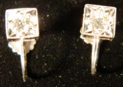 A pair of 9 ct white gold earrings Each of square form with a screw fixing.