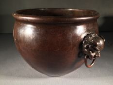 A Chinese cast bronze censor The body with temple dog mask ring handles,