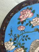 A Chinese cloisonne plate Typically decorated with cranes in a river landscape with floral sprays.