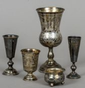 Four various Russian silver cups and a Russian silver salt The largest 14 cm high.
