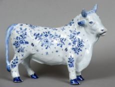 A Continental blue and white tin glazed pottery figure of a bull Decorated with floral sprays.