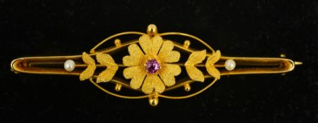 An Edwardian 15 ct gold pink sapphire and seed pearl set floral brooch 5.5 cm wide.