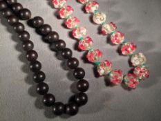 A string of Chinese coloured glass beads  With applied floral decoration;