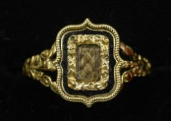 A Georgian unmarked gold mourning ring Centrally set with a hair plait bordered by an enamel band.