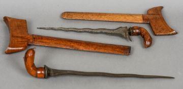 Two Indonesian kris Each with carved wood handle, typically shaped blade and wooden scabbard.