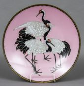 A Japanese Meiji cloisonne charger Decorated with three cranes before a pink background.