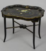 A Victorian lacquered papier mache tray  Mounted on a later fitted stand,