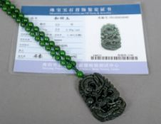A well carved green jade pendant Decorated with a dragon chasing a flaming pearl,