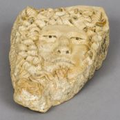 A carved stone satyr mask 31 cm high.
