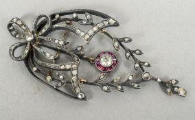 A Victorian unmarked diamond and ruby set pendant brooch Of pierced trailing foliate form.