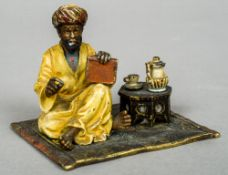 A cold painted bronze model of an Arab figure  Seated on a rug taking tea.  8.5 cm wide.