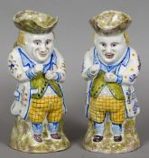 Two similar Continental tin glazed pottery snuff taker Toby jugs Each typically modelled,