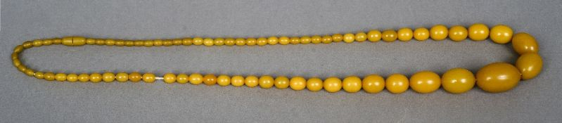 A string of yellow amber beads Of varying size.  67 cm long.
